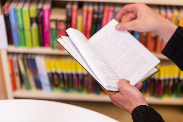 Un vecchio uomo che legge un libro in biblioteca. girando pagina, messa a fuoco selettiva, mani in alto