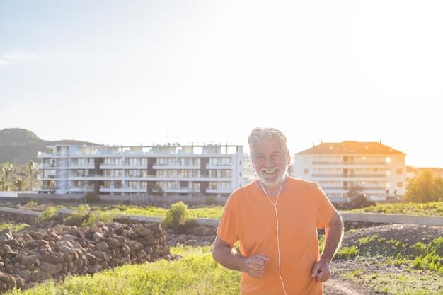 Vecchio o anziano che corre da solo in una zona rurale intorno alla natura e alle case - un maschio maturo che fa esercizio e perde peso