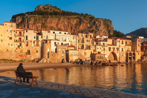 Vecchio seduto sulla panchina e godendo di una splendida vista della città costiera di cefalù al tramonto, sicilia, italia