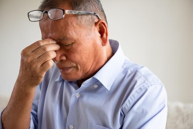 Uomo anziano che si siede sul sofà e che ha un'emicrania a casa. concetto di assistenza sanitaria senior.