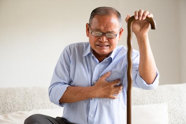 Uomo anziano che si siede sul sofà e che ha a con dolore sul cuore. concetto di assistenza sanitaria senior.
