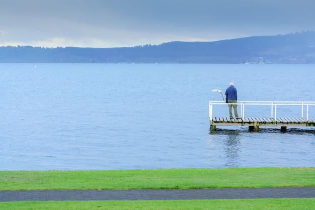 Il vecchio uomo in piedi sul ponte sul lago taupo, isola del sud della nuova zelanda