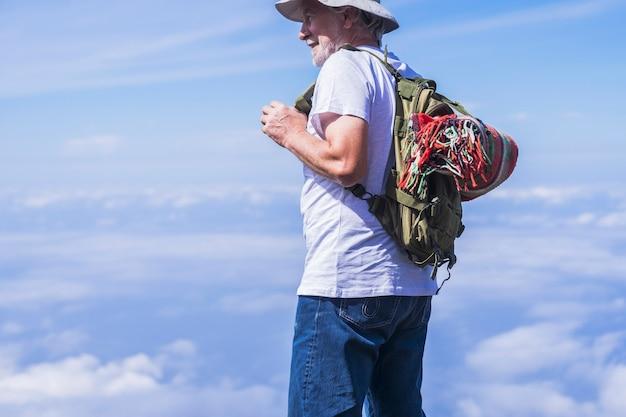 Il ritratto di un vecchio viaggiatore si gode la vista delle nuvole in alto - zaino e coperta colorata in stile retrò sul retro. stile di vita felice e persone moderne - maschio maturo anziano in attività di svago all'aperto