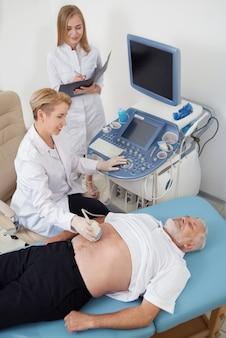 Uomo anziano su diagnostica per ultrasuoni in studio medico.