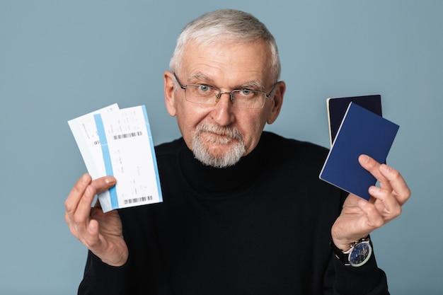 Uomo anziano con biglietti aerei e ritratto del passaporto