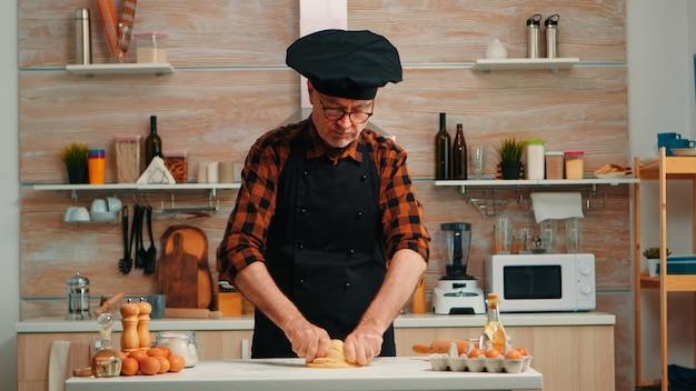 Uomo anziano con grembiule da cucina che cucina il pane nella cucina moderna a casa. fornaio anziano in pensione con bonete che mescola ingredienti con farina di grano setacciata che si impasta per la cottura di torte e pane tradizionali