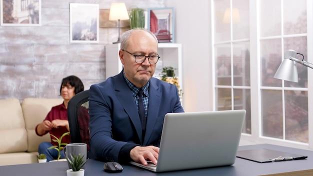 Vecchio che lavora al computer portatile e beve un sorso di caffè in soggiorno con la moglie seduta sul divano sullo sfondo.