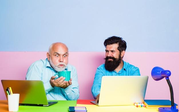 Vecchio manager che ha una conversazione amichevole durante l'incontro con laptop vecchi e giovani uomini d'affari usando la nota...