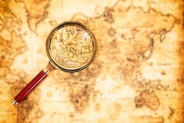 Vecchia mappa con una lente di ingrandimento che la esplora. sfondo di viaggio vintage