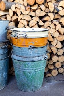 Vecchi secchi di metallo si trovano nel capannone vicino a una catasta di legna da ardere tagliata