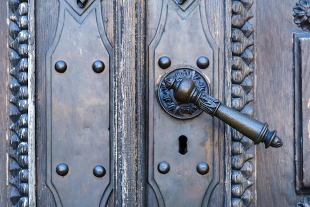Vecchia maniglia della porta in metallo sulla vecchia porta