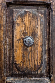 Una vecchia maniglia della porta di metallo sulla vecchia porta di legno