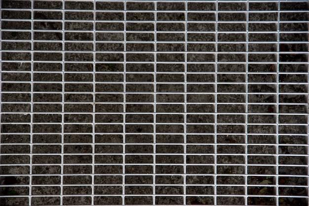Vecchia grata metallica nel marciapiede. la garza metallica di un drenaggio, close-up, vista dall'alto, flat lay