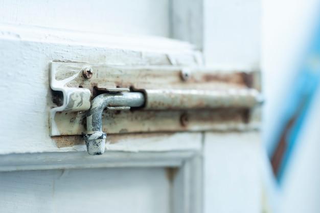 Il vecchio fermo in metallo è di colore bianco macchiato dalla pittura della porta
