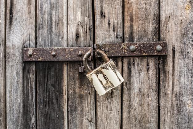 Il vecchio metallo fissa la vecchia porta di legno