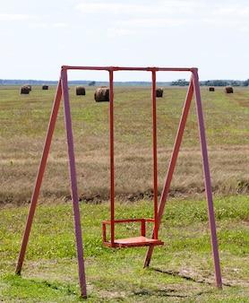 Vecchia altalena in metallo sul campo, tempo nuvoloso in autunno o in tarda estate
