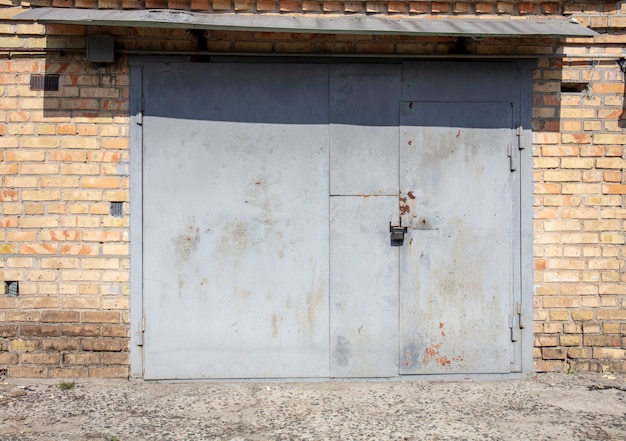 Vecchio capannone della porta del magazzino in metallo