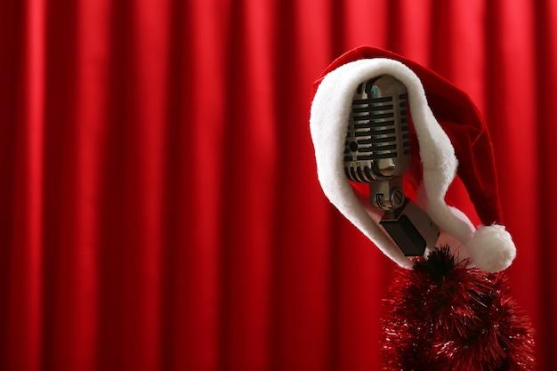Vecchio microfono decorato con cappello di natale e trombetta sullo sfondo della tenda rossa