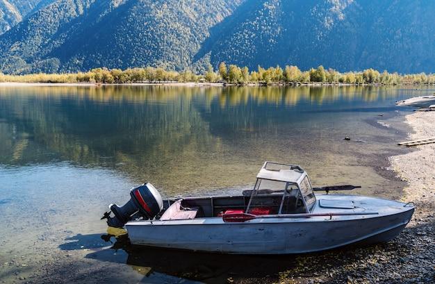 Vecchia barca a motore vicino alla riva del lago di montagna. autunno. russia, altai, lago teletskoye