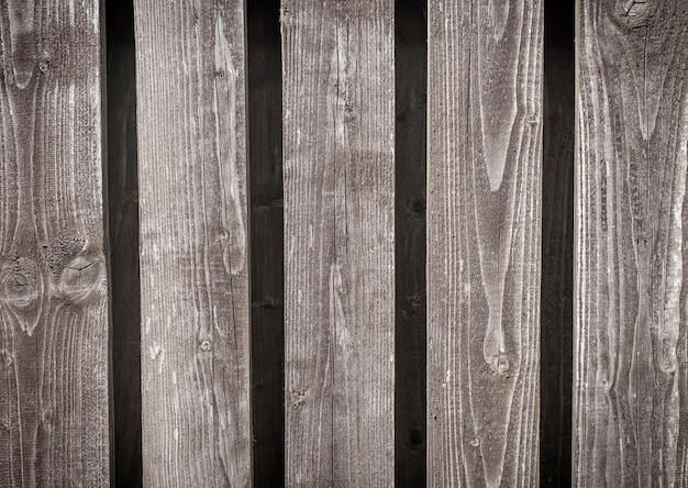 Vecchio fondo di recinzione di legno grigio naturale con assi verticali