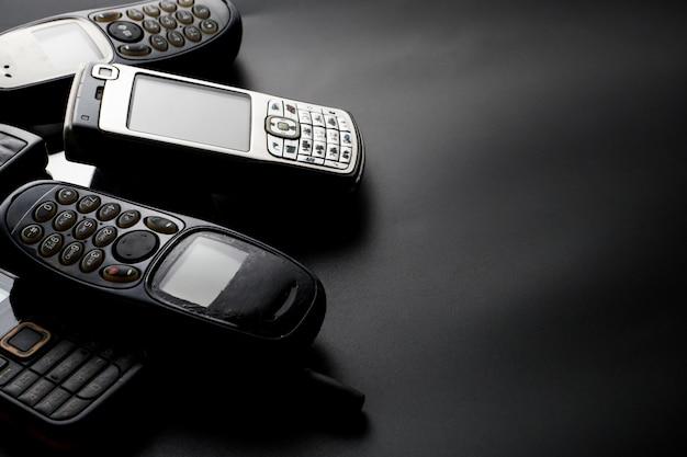 Cellulari vecchi e obsoleti su sfondo nero.