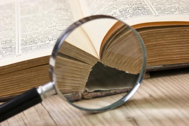Vecchio libro aperto e lente d'ingrandimento