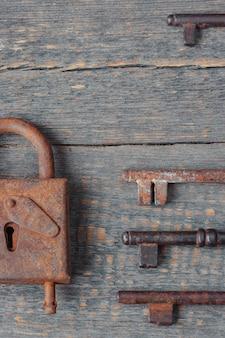Il vecchio lucchetto e le chiavi si trovano su una tavola di legno