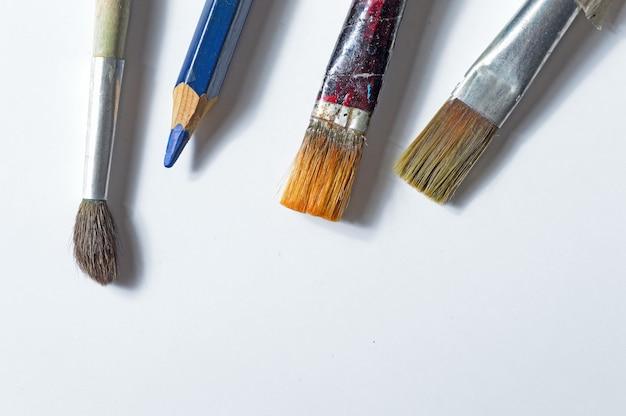 Vecchi pennelli su uno sfondo bianco.