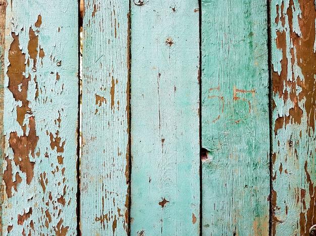 Vecchia struttura di tavole dipinte. primo piano dei vecchi pannelli di recinzione in legno verde