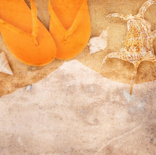 Vecchio sfondo di carta con sandali e conchiglie sulla sabbia