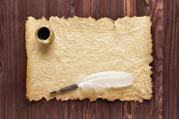 Vecchia carta e calamaio con penna d'oca su uno sfondo di legno