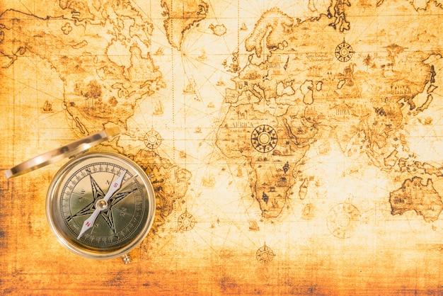 Vecchia mappa cartacea con un'antica bussola su di essa. sfondo di viaggio vintage