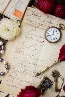 Vecchia carta con macchie di inchiostro e vecchia lettera con orologio antico e penna piuma