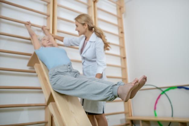 Vecchio paziente che esercita in un centro di riabilitazione con istruttore