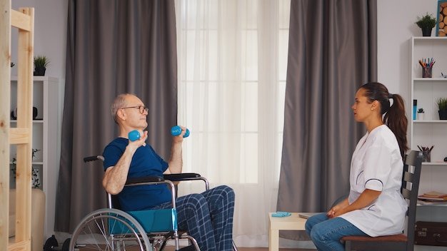 Paziente anziano in sedia a rotelle che fa riabilitazione con il supporto dell'infermiera. persona anziana portatrice di handicap con assistente sociale in terapia di supporto per il recupero fisioterapia sistema sanitario infermieri pensionati