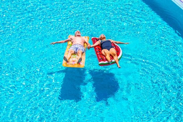 Le coppie senior delle persone anziane si rilassano e dormono sull'acqua limpida della piscina blu sdraiati sul materasso gonfiabile colorato alla moda e prendendo le mani con amore per il concetto di stile di vita per sempre insieme