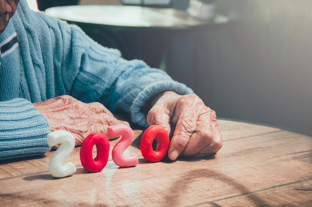 La persona anziana passa il numero 2020 della tenuta sulla tavola di legno. concetto: la popolazione più anziana del mondo da 2020 anni cresce in modo drammatico.