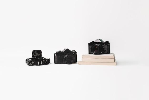 Vecchie macchine fotografiche con libri isolati su bianco