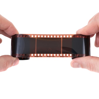 Vecchia pellicola fotografica nelle mani su sfondo bianco
