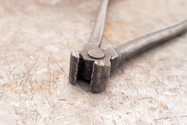 Vecchie tenaglie giacciono su una superficie di metallo arrugginita e squallida
