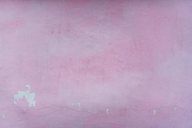 Vecchio muro rosa con intonaco incrinato sullo sfondo