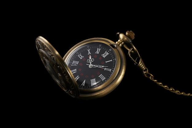 Vecchio orologio meccanico da tasca isolato su sfondo nero. accessorio alla moda e antico.