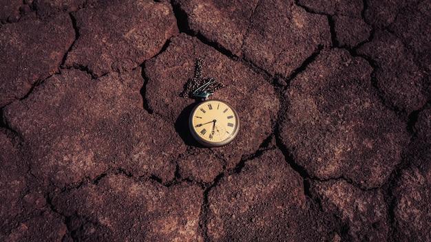 Un vecchio orologio da tasca giace su un terreno asciutto. passato e futuro.