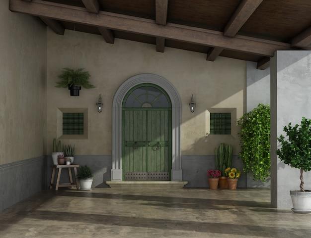 Vecchio portico di una casa di campagna con grande porta d'ingresso, due piccole finestre e soffitto in legno