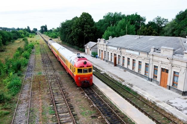 Vecchia stazione ferroviaria con treni passeggeri e ferrovie di fronte