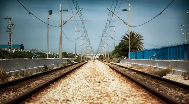 Una vecchia ferrovia alla stazione ferroviaria di tunisi, nord africa. piattaforma ferroviaria con rotaie e cavi elettrici. vista del paesaggio della strada in uscita