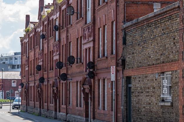 Vecchio edificio in mattoni rossi con molti piatti satellitari sulle pareti.
