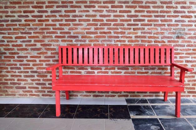Vecchia sedia da banco lunga rossa sul pavimento di cemento e vecchio muro di mattoni.