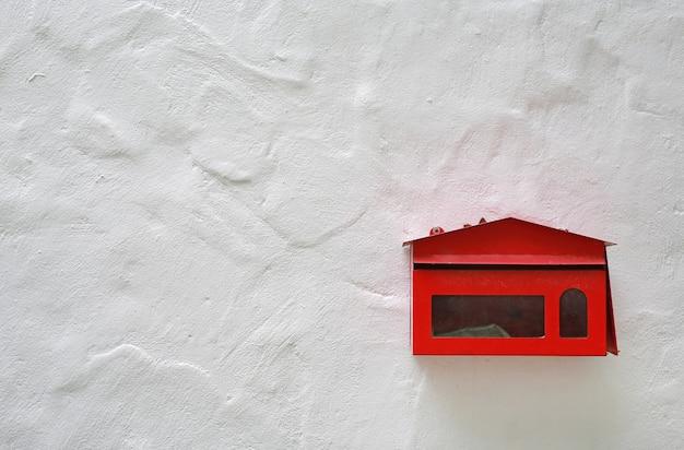 La vecchia cassetta delle lettere rossa ha montato su una parete del cemento con lo spazio della copia.