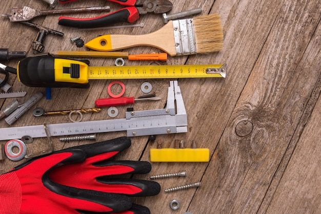 Vecchi strumenti di riparazione su uno sfondo di legno.